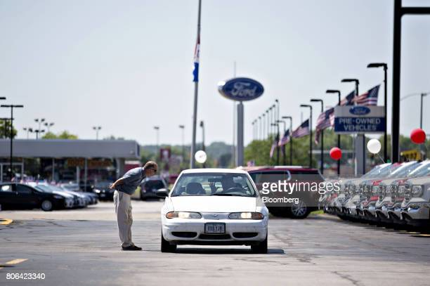 A salesman talks to a person in a vehicle at a Fiat Chrysler Automobiles car dealership in Moline Illinois US on Saturday July 1 2017 Ward's...