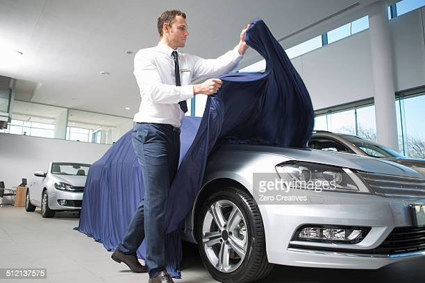 Salesman uncovering new car in car dealership