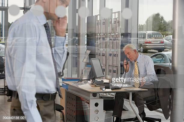 Salesman using phone at desk in car showroom, man in foreground