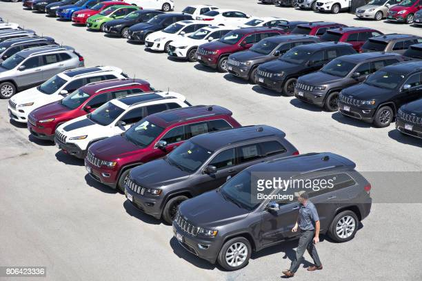 A salesman walks near a row of Fiat Chrysler Automobiles 2017 Jeep Cherokee and Grand Cherokee vehicles for sale at a car dealership in Moline...