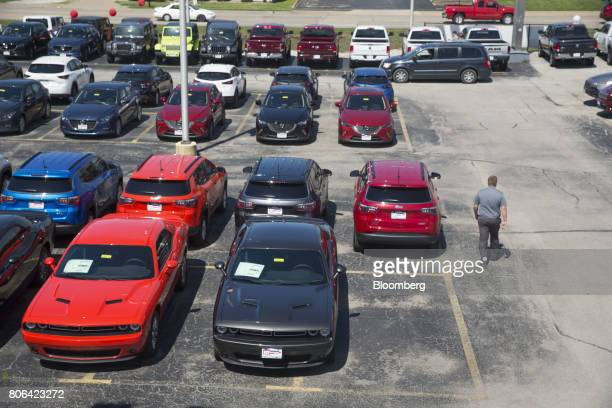 A salesman walks past a row of Fiat Chrysler Automobiles Dodge Challenger vehicles displayed for sale at a car dealership in Moline Illinois US on...