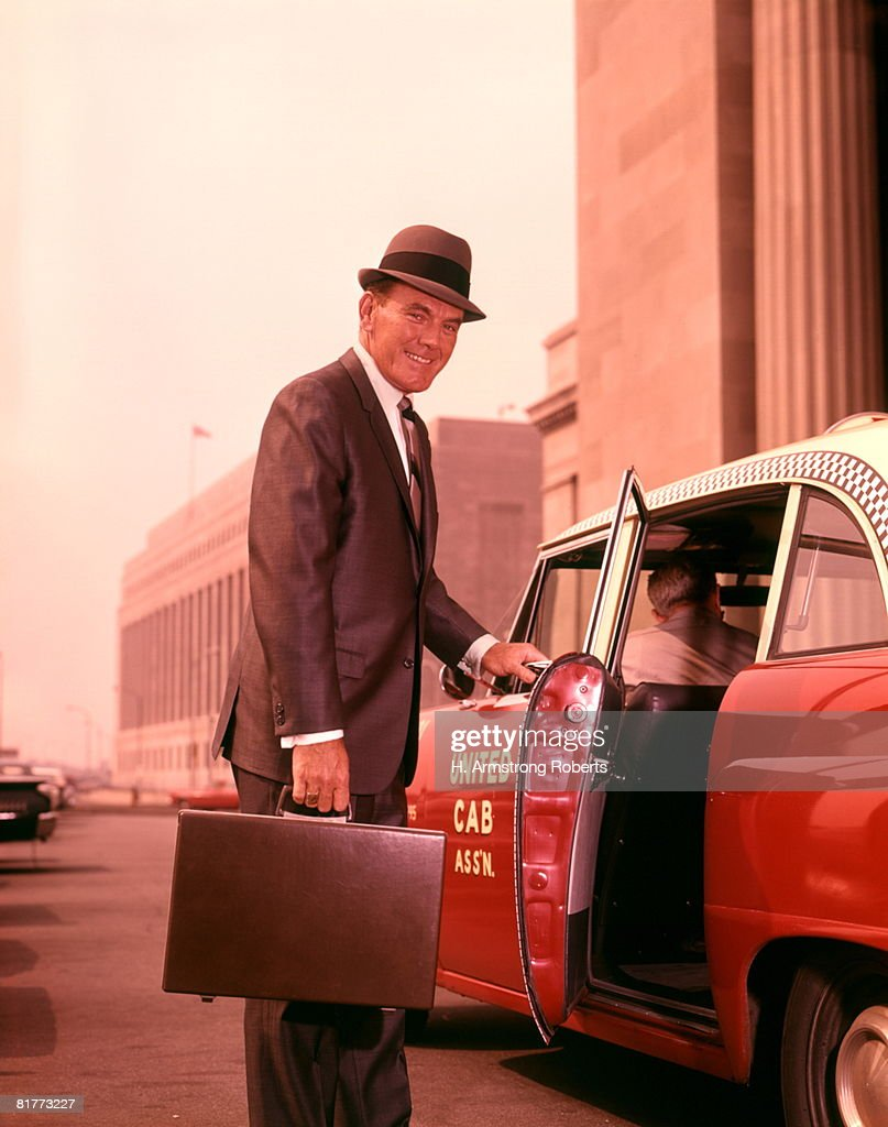 Salesman With Attache Case About To Enter Taxi Cab At Train Station. : Stock Photo