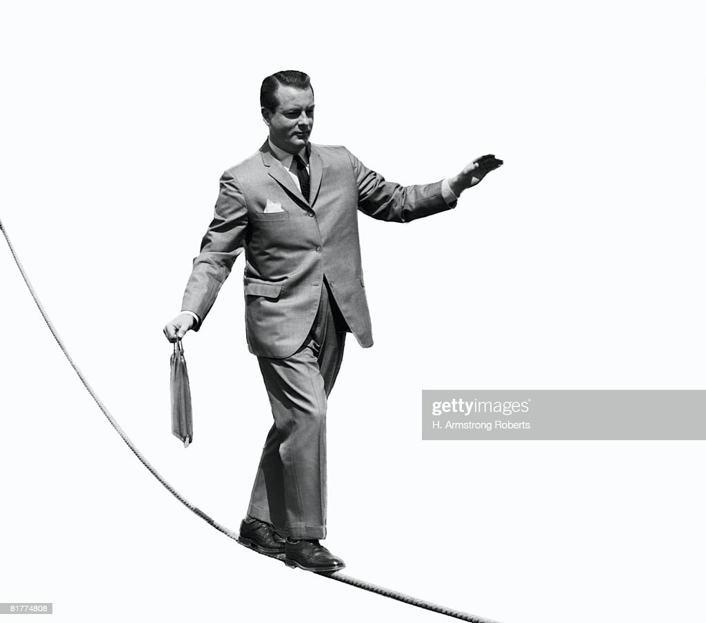 Salesman with briefcase walking tightrope. : Stock Photo