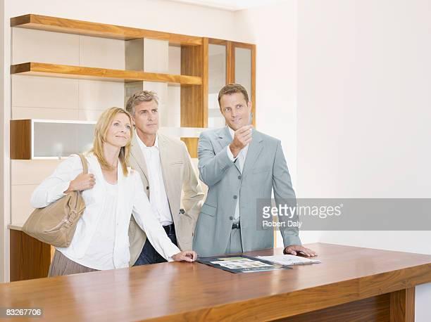 Salesman with couple in interior design showroom