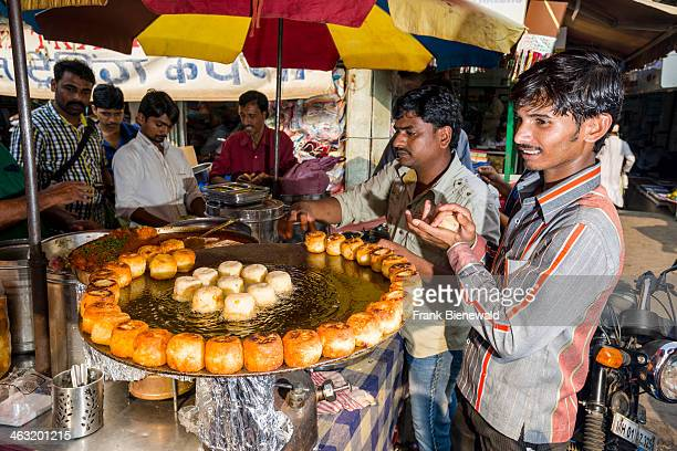Salesmen are offering snacks for sale in a crowded street with shops at Mangaldas Market