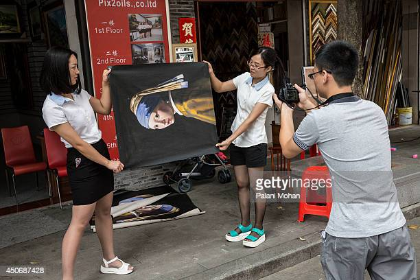 Salespeople roll out a reproduction of the famous work 'Girl with a Pearl Earring' at the artist village on June 11 2014 in Shenzhen China The Dafen...