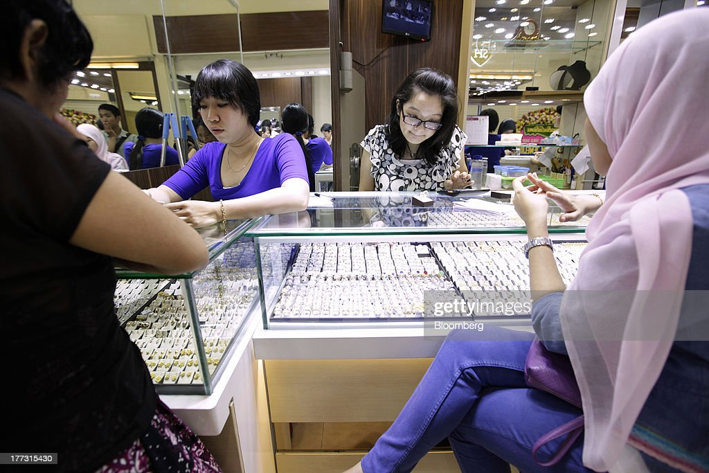Salespeople serve customers at a jewelry store in Jakarta, Indonesia, on Thursday, Aug. 22, 2013. Gold jewelry demand in Indonesia is set to expand to a four-year high as consumers in Southeast Asia's biggest buyer join India to China in increasing purchases as prices slump and the middle class expands. Photographer: Dimas Ardian/Bloomberg via Getty Images