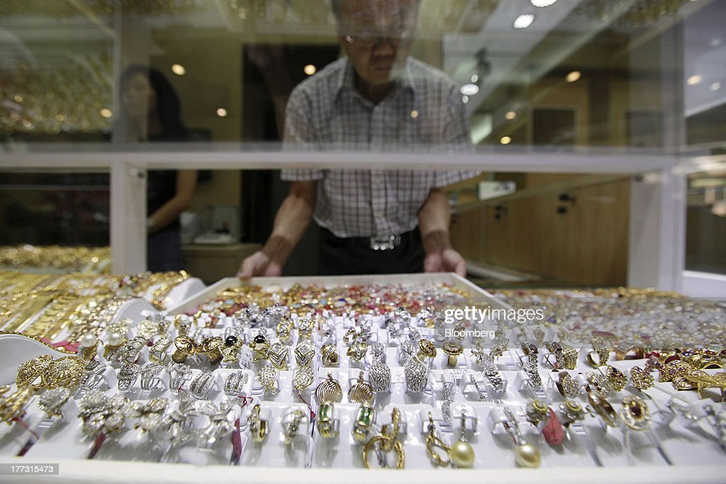 A salesperson arranges a tray of jewelry in a display cabinet at a jewelry store in Jakarta, Indonesia, on Thursday, Aug. 22, 2013. Gold jewelry demand in Indonesia is set to expand to a four-year high as consumers in Southeast Asia's biggest buyer join India to China in increasing purchases as prices slump and the middle class expands. Photographer: Dimas Ardian/Bloomberg via Getty Images