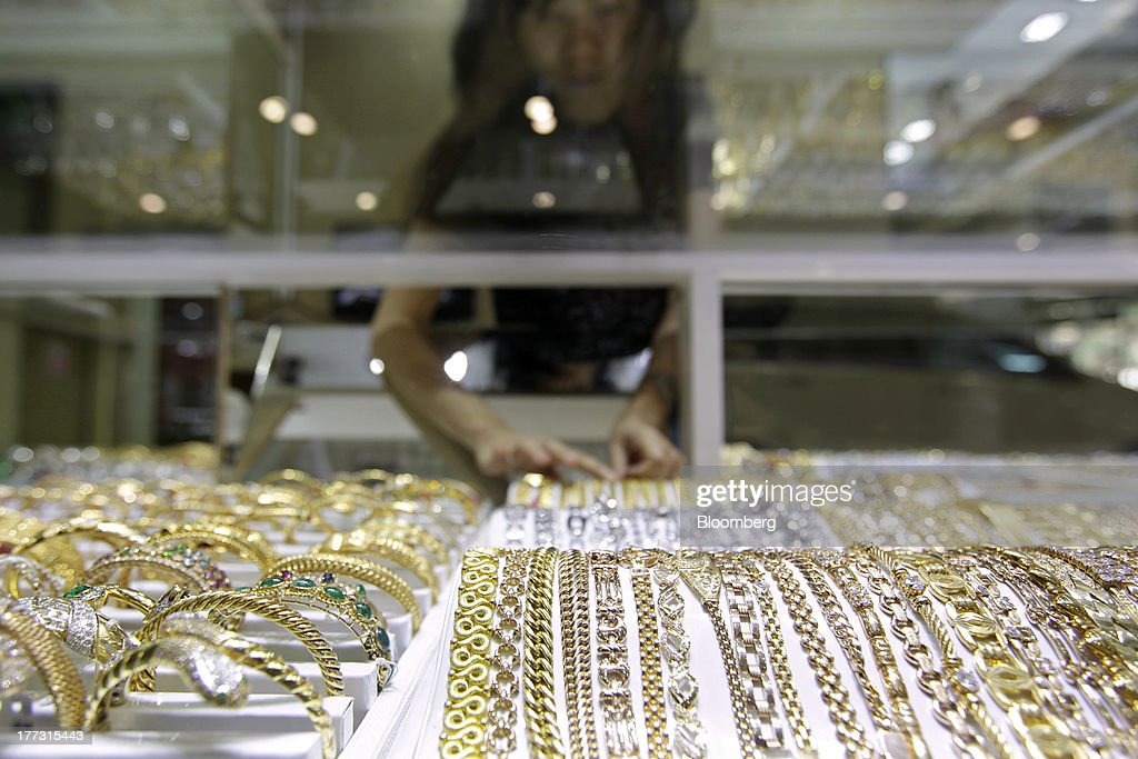 A salesperson arranges jewelry in a display cabinet at a jewelry store in Jakarta, Indonesia, on Thursday, Aug. 22, 2013. Gold jewelry demand in Indonesia is set to expand to a four-year high as consumers in Southeast Asia's biggest buyer join India to China in increasing purchases as prices slump and the middle class expands. Photographer: Dimas Ardian/Bloomberg via Getty Images