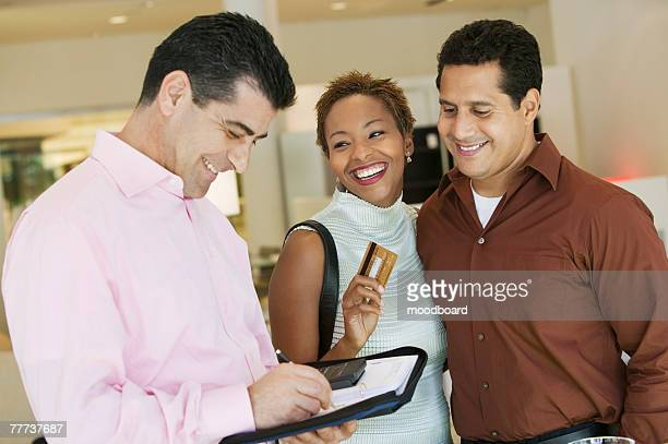 Salesperson Calculating Couple's Purchase Amount