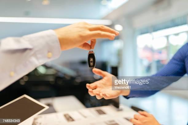 Salesperson handing over car keys to customer