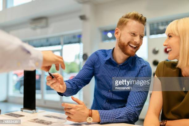 Salesperson handing over car keys to customers