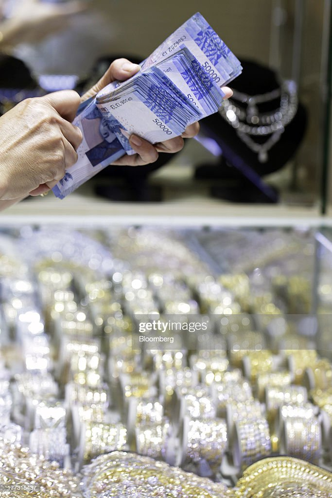 A salesperson handles rupiah banknotes at a jewelry store in Jakarta, Indonesia, on Thursday, Aug. 22, 2013. Gold jewelry demand in Indonesia is set to expand to a four-year high as consumers in Southeast Asia's biggest buyer join India to China in increasing purchases as prices slump and the middle class expands. Photographer: Dimas Ardian/Bloomberg via Getty Images