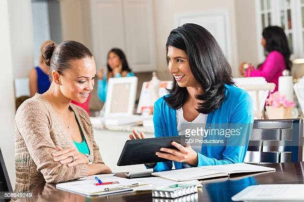 Salesperson placing order on digital tablet during jewelry party