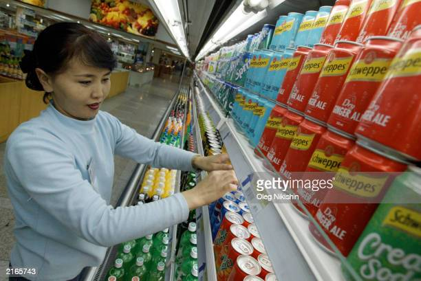 A salesperson puts products in a display case in a modern western style 'Sky' supermarket July 16 2003 in Ulan Bator Mongolia This private...