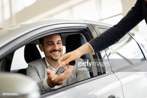 Salesperson selling cars at car dealership : Stock Photo