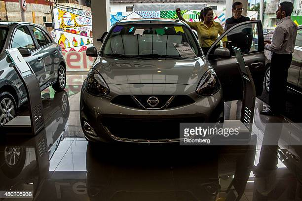 A salesperson shows a car to a couple at a Nissan Motor Co auto dealership in the Botafogo neighborhood of Rio de Janeiro Brazil on Thursday July 9...