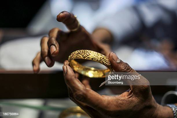 A salesperson shows a gold bangle at the Dwarkadas Chandumal Jewelers store during the festival of Dhanteras two days before Diwali in the Zaveri...