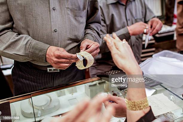 A salesperson shows gold bangles to a customer at the Dwarkadas Chandumal Jewellers store in the Zaveri Bazaar area of Mumbai India on Thursday April...