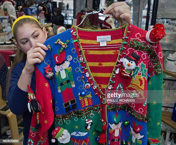 Salesperson Sissi Terryberry displays a tacky Christmas Sweater with lights and bells at the consignment store ReLove It on December 23 2014 in...
