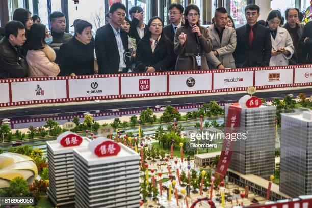 A salesperson speaks to prospective customers looking at a model of the Dalian Wanda Group Co Oriental Movie Metropolis at a real estate showroom...