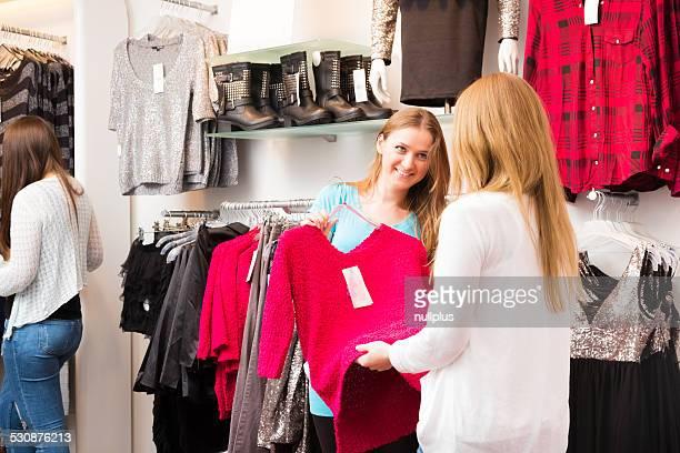 Verkäufer im Gespräch mit Kunden in Mode speichern