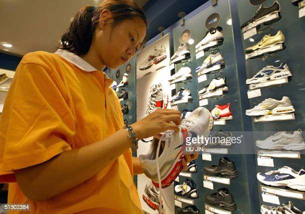 A saleswoman adjusts shoelace of a sports shoe at a Nike store in Shanghai 14 September 2004 China's retail sales rose 131 percent yearonyear in...