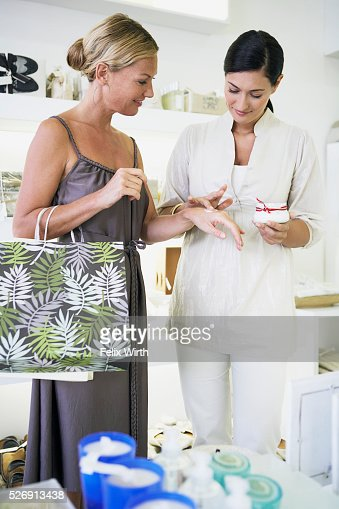Saleswoman applying lotion to customer's hand : Foto stock
