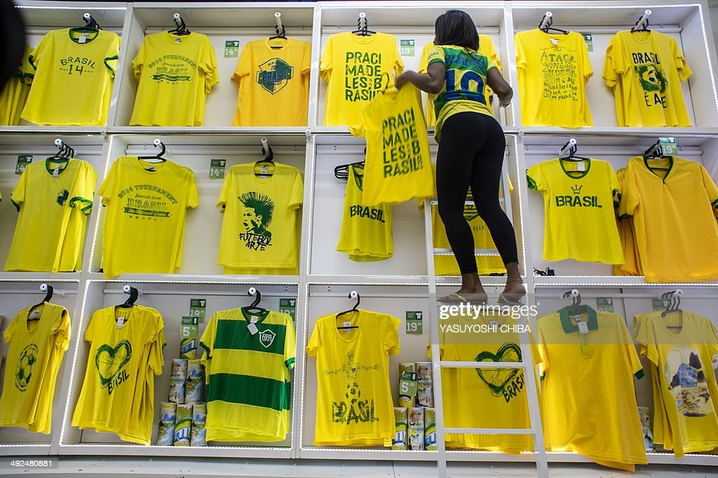 A saleswoman arranges Tshirts fro sale designed for Brazilian fans for the FIFA World Cup 2014 at a store in Rio de Janeiro Brazil on May 20 2014...