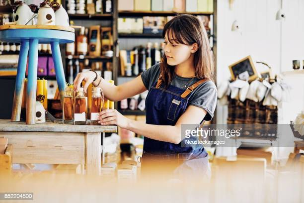 Saleswoman arranging infused oil bottles on counter in deli store