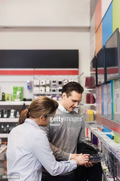 Saleswoman assisting male customer in buying phone cover at store