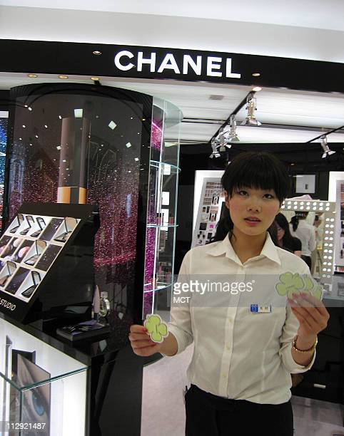 A saleswoman at a Chanel perfume boutique in a Tokyo department store beckons clients with aroma samples June 29 2007
