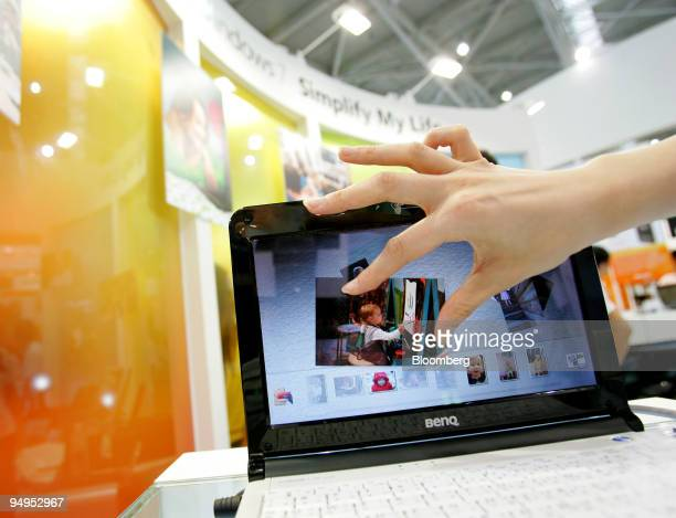 A saleswoman displays a Microsoft Corp multitouchenabled computer installed with Windows 7 during the Computex Technology Expo in Taipei Taiwan on...