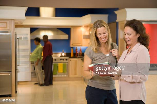 Saleswoman helping customer in kitchen showroom