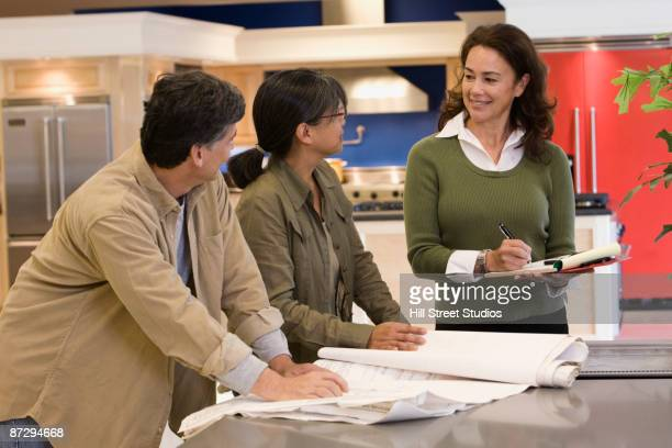 Saleswoman helping customers in kitchen showroom