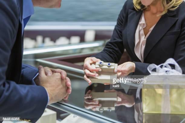 Saleswoman helping man shop for jewelry