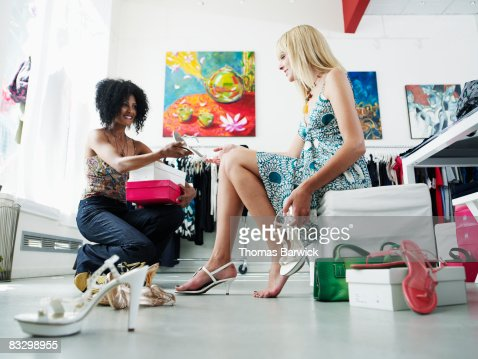 Saleswoman helping woman try on shoes in boutique