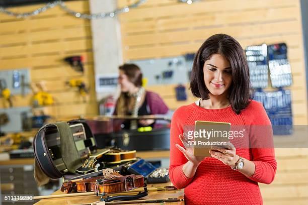 Verkäuferin in kleinen Unternehmen, das sich verkauft, und Reparaturen Musikinstrumente
