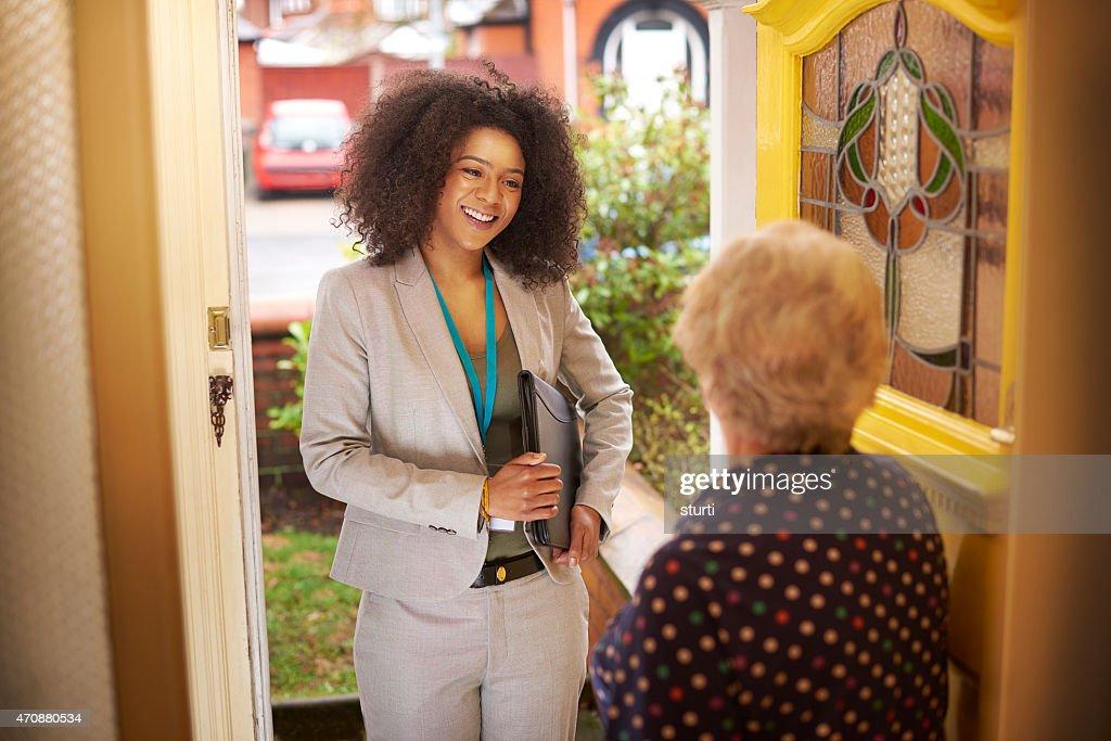 Saleswoman introduces herself to senior woman at the door