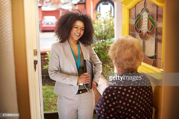 Saleswoman präsentiert sich senior Frau an der Tür