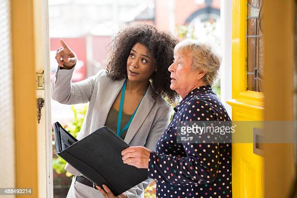 saleswoman  pointing out work to householder