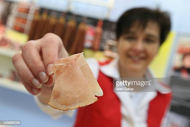A saleswoman presents the photographer with a slice of dried ham at the 2013 Gruene Woche agricultural trade fair on January 18 2013 in Berlin...