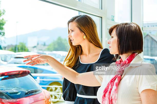 Saleswoman selling car to woman