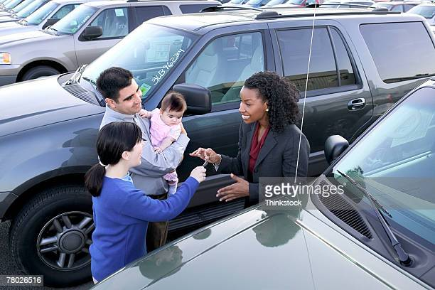 A saleswoman smiles as she hands over the keys of a new car to a young family