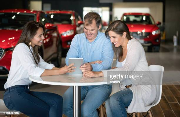 Saleswoman talking to a couple at the car dealership