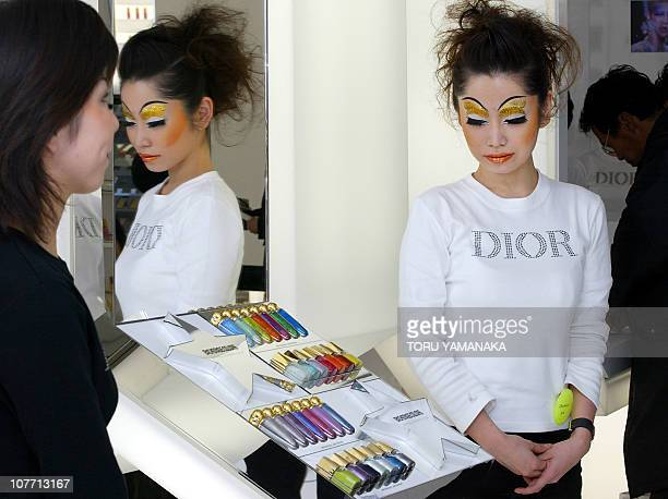 A saleswoman waits for customers during the opening of the Christian Dior flagship boutique at Tokyo's fashion district Harajuku 07 December 2003 AFP...