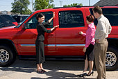 Saleswoman with couple by SUV