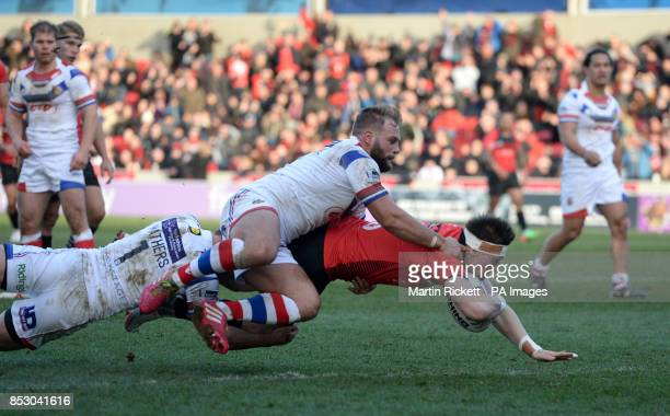 Salford Red Devils' Andrew Dixon goes over for a try past Wakefield Trinity Wildcats' Paul McShane and Richard Mathers during the Super League match...