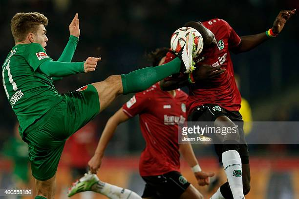 Salif Sane of Hannover and Alexander Esswein of Augsburg compete for the ball during the Bundesliga match between Hannover 96 and FC Augsburg at...