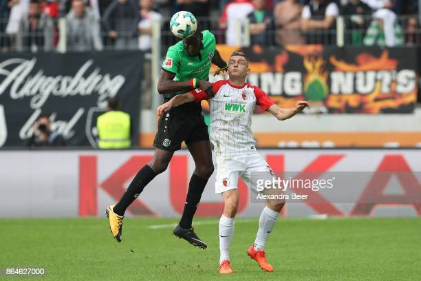 Salif Sane of Hannover fights for the ball with Alfred Finnbogason of Augsburg during the Bundesliga match between FC Augsburg and Hannover 96 at...